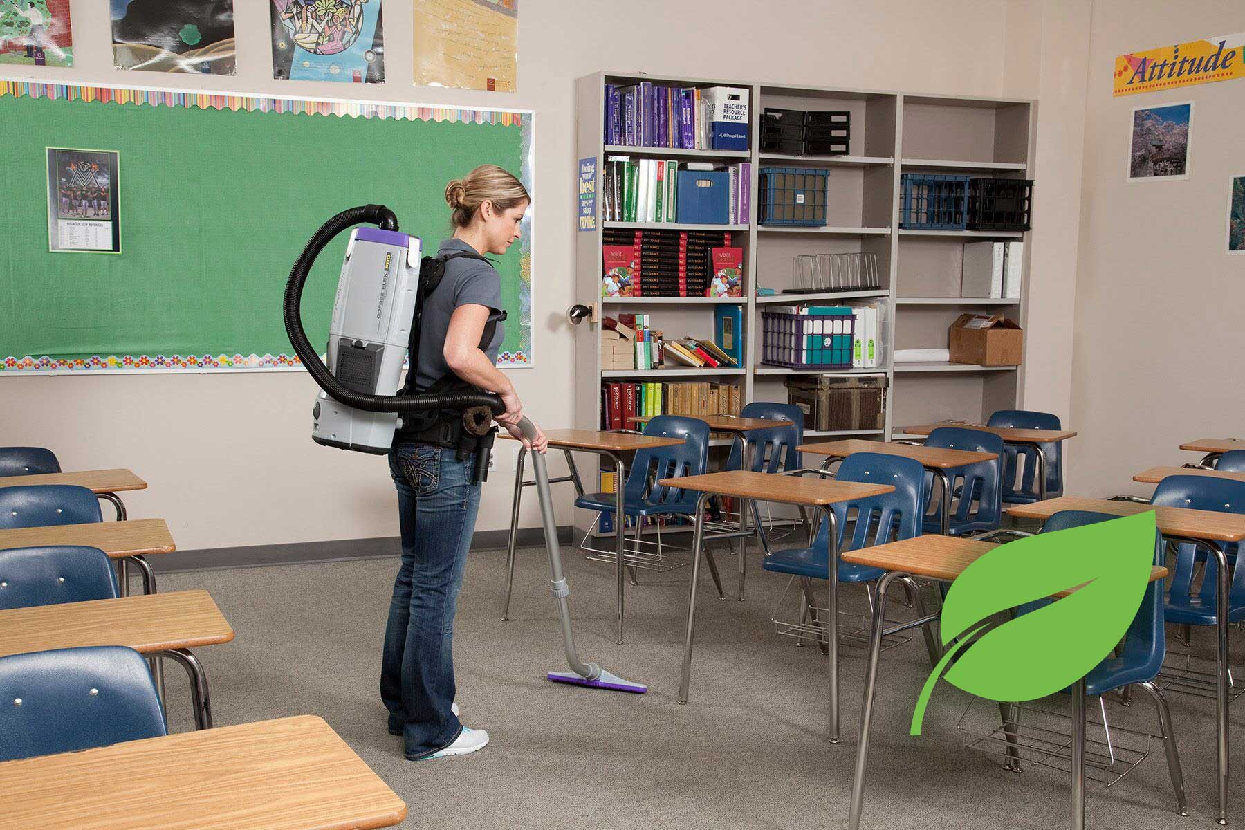 woman vacuuming inside classroom showcasing Green Cleaning Services
