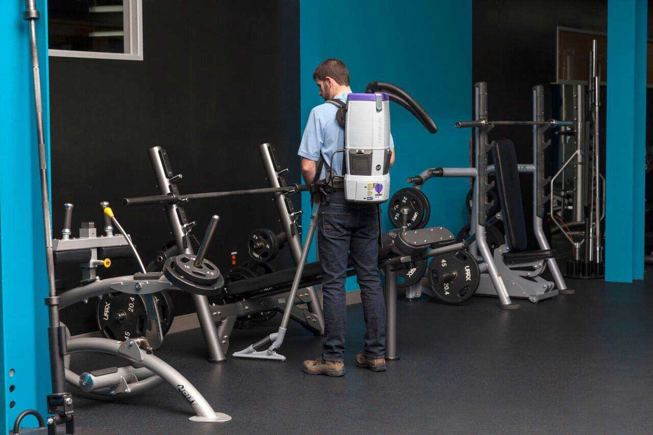 man vacuuming inside workout room showcasing Cleaning Services