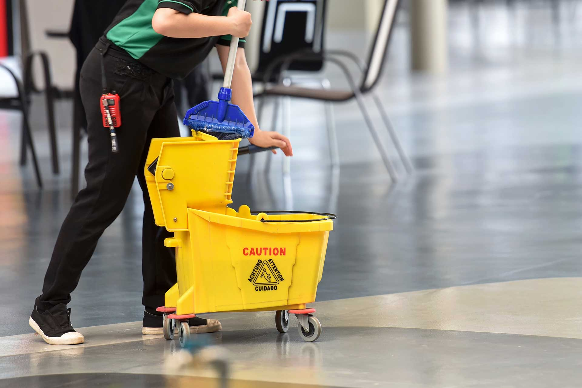 person with yellow floor mopping container